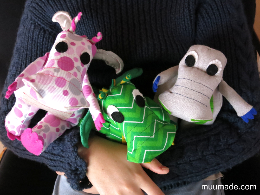 Dragon and dinosaur stuffed animals in the arms of a child