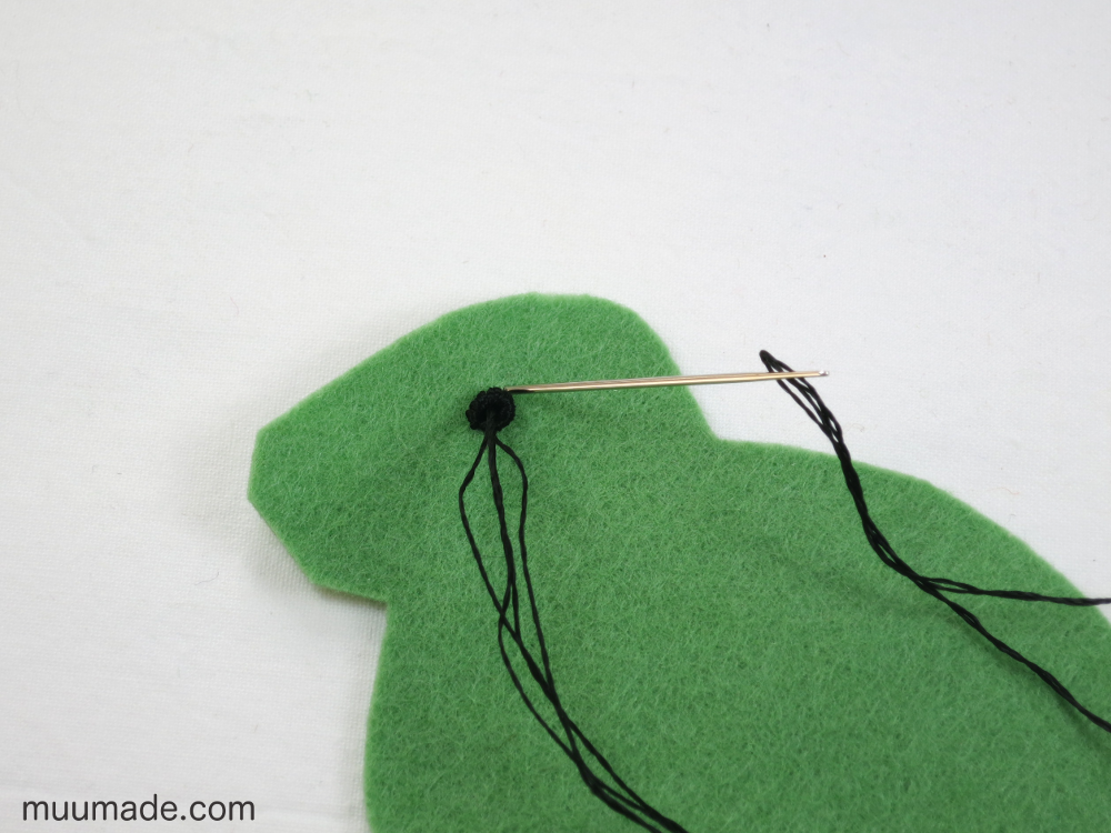 A felt bunny's eye being sewn on