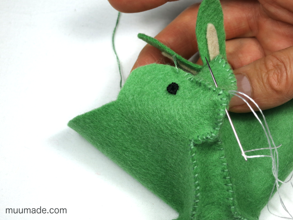 A green felt bunny being sewn