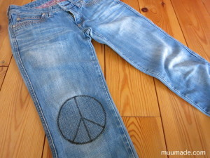 Jeans with a DIY peace symbol knee patch