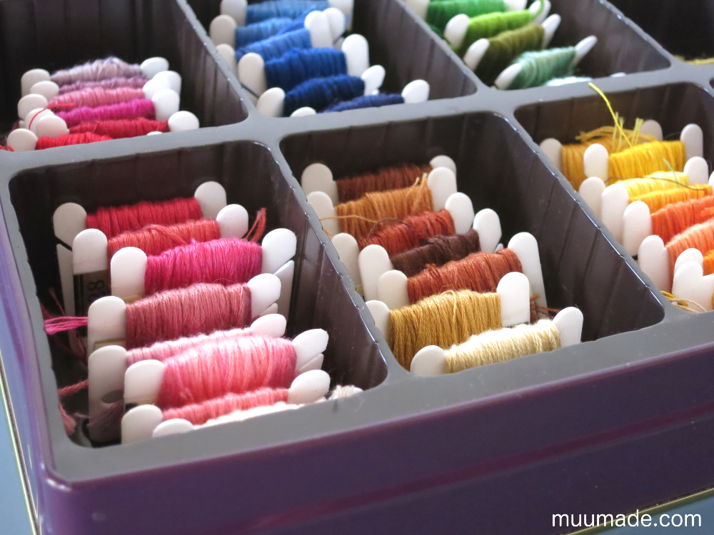Embroidery threads neatly organized in a tin with dividers