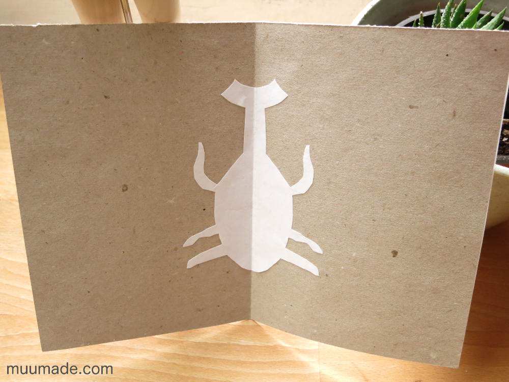 Handmade paper cut out card - a white cut out beetle against a light brown background