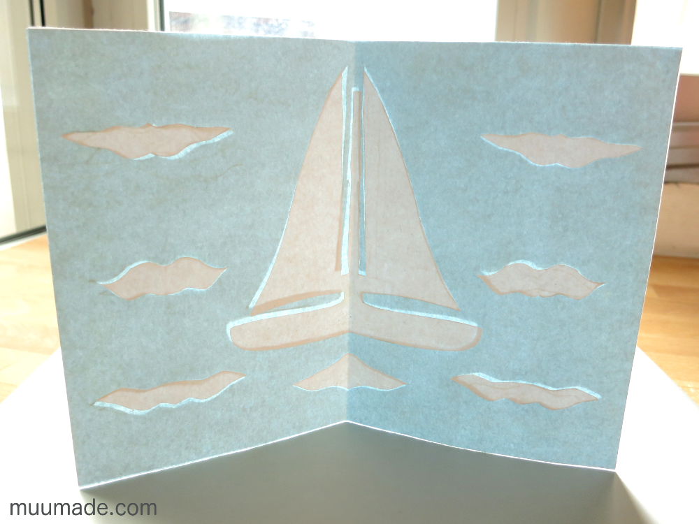 Handmade paper cut out card - a white sail boat, waves and clouds again a light blue background