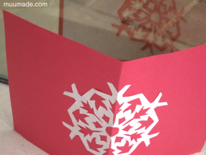 Handmade paper cut out card - a white snowflake against a red background