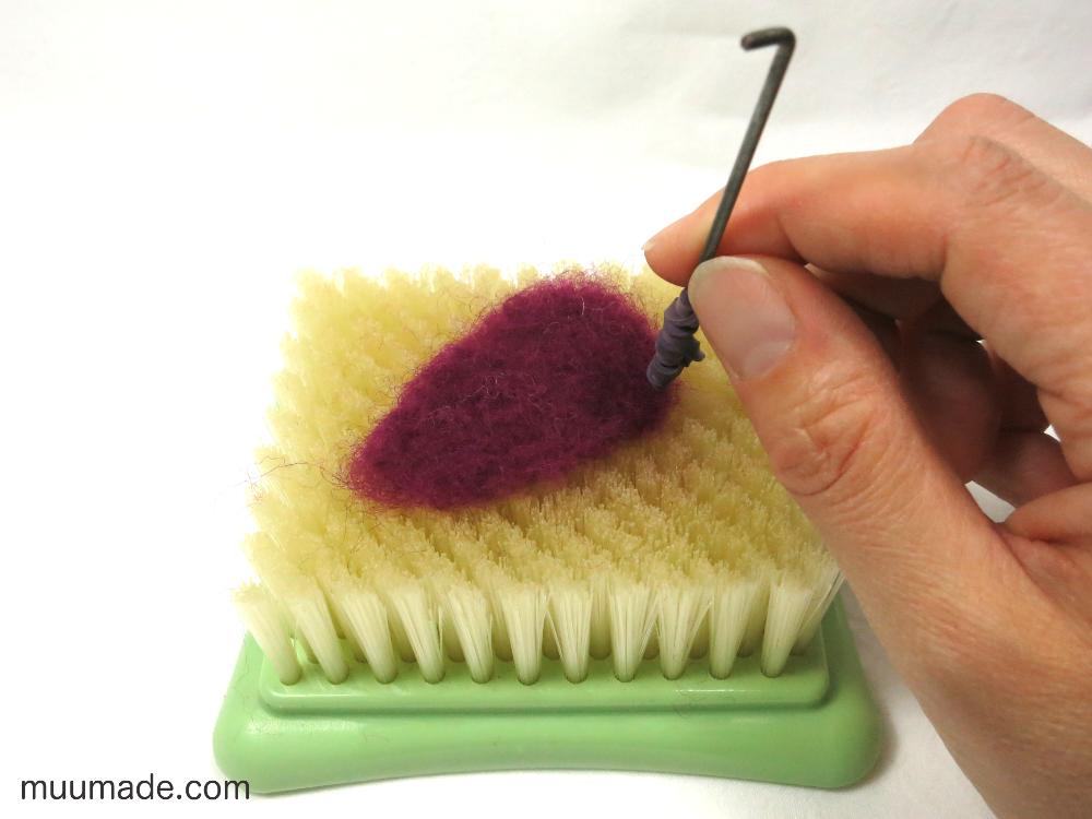 Needle felting on a brush mat